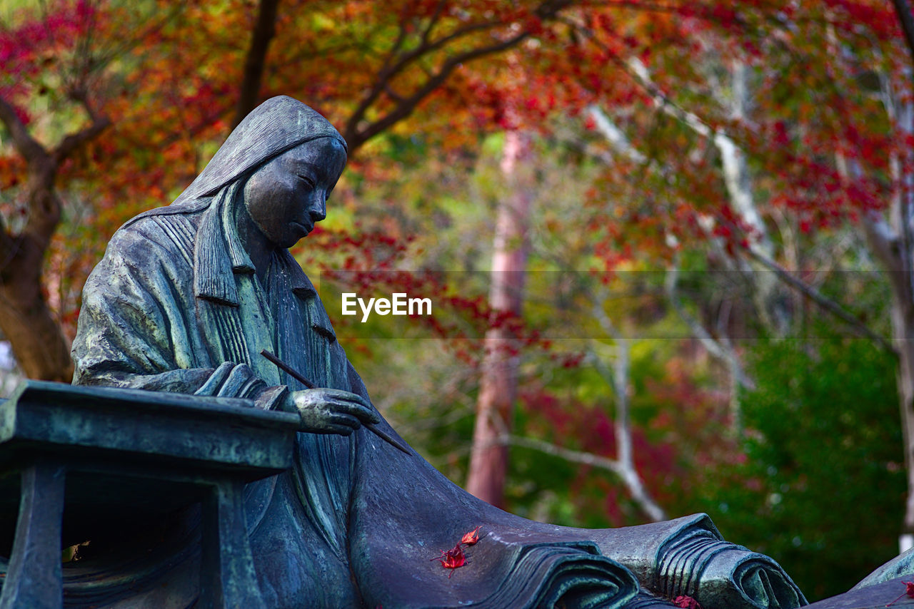 Low Angle View Of Statue Against Trees During Autumn