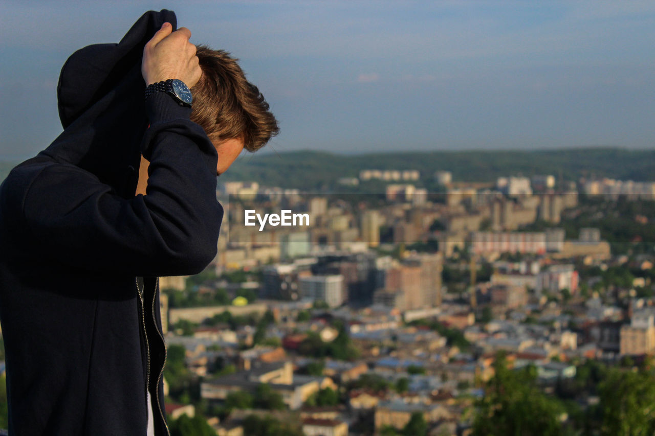 Side view of man wearing black hooded jacket against cityscape