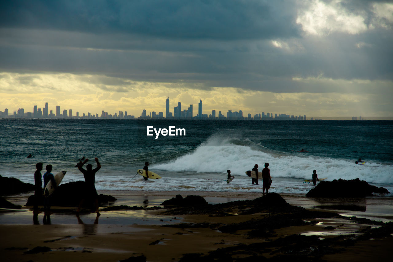 People Enjoying At Beach By City Against Cloudy Sky During Sunset