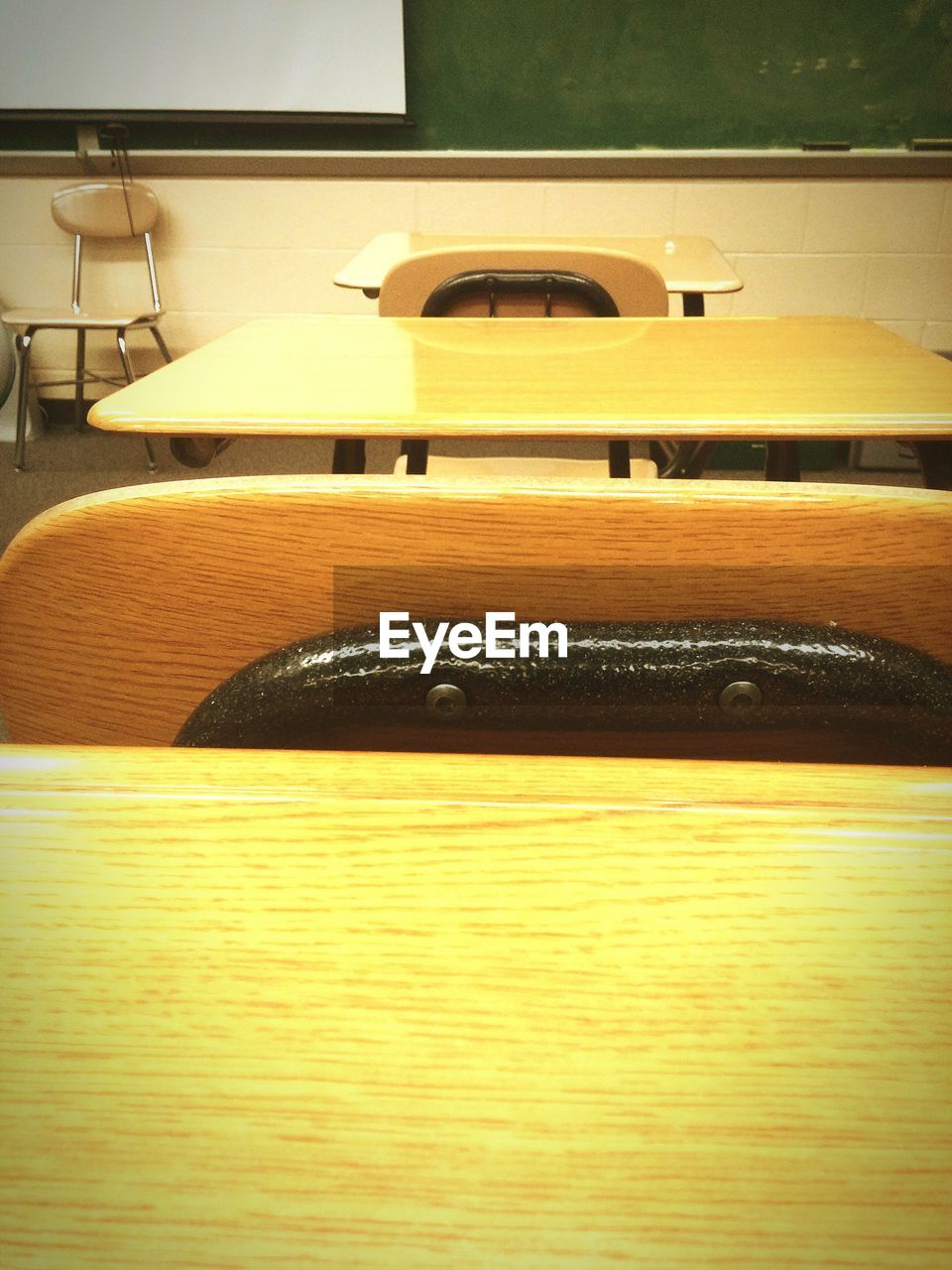 Close-up of chairs and wooden tables arranged in classroom