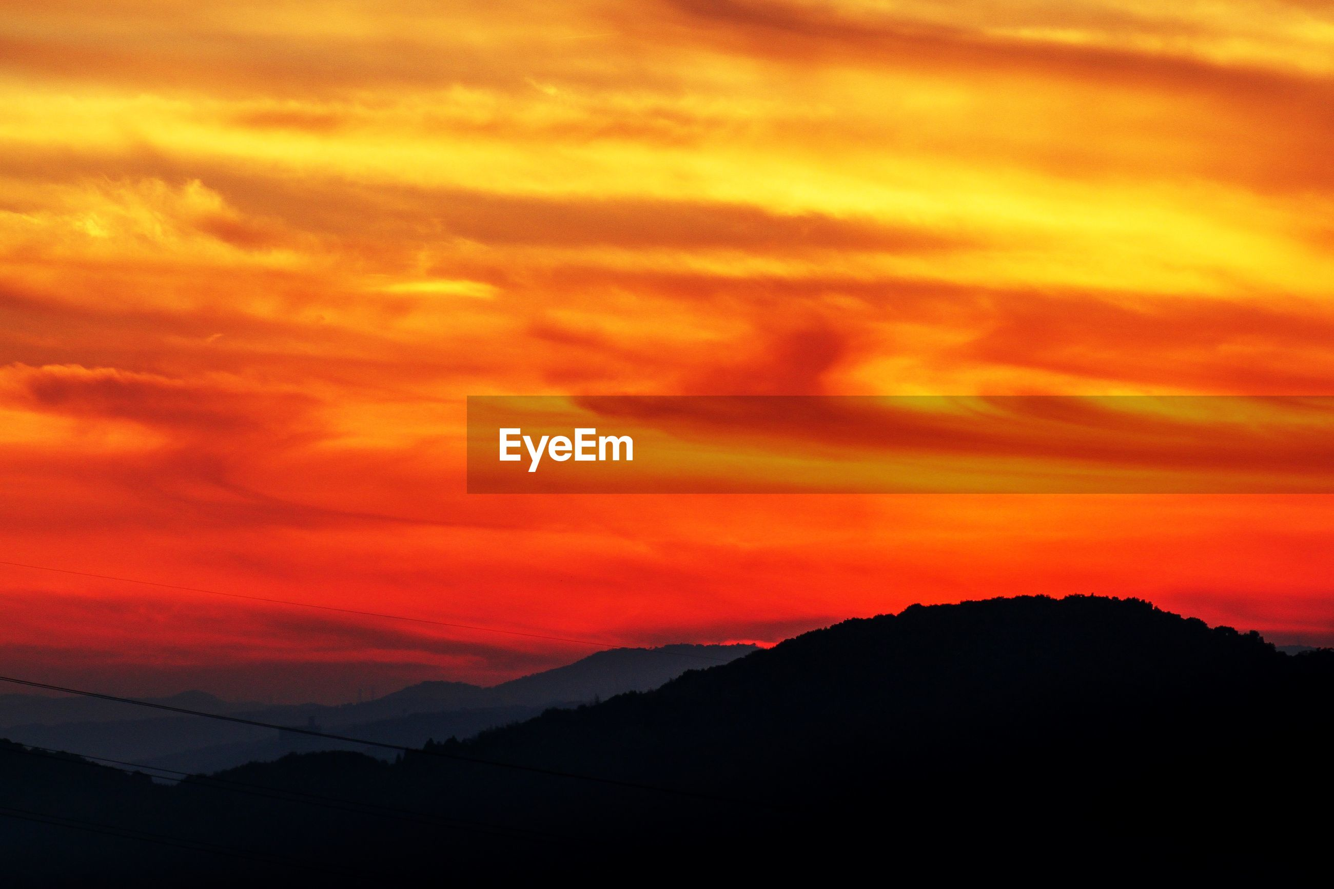 Scenic view of silhouette mountains against orange cloudy sky