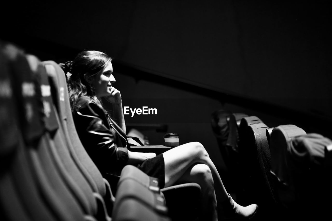 Side view of woman watching a movie in a cinema