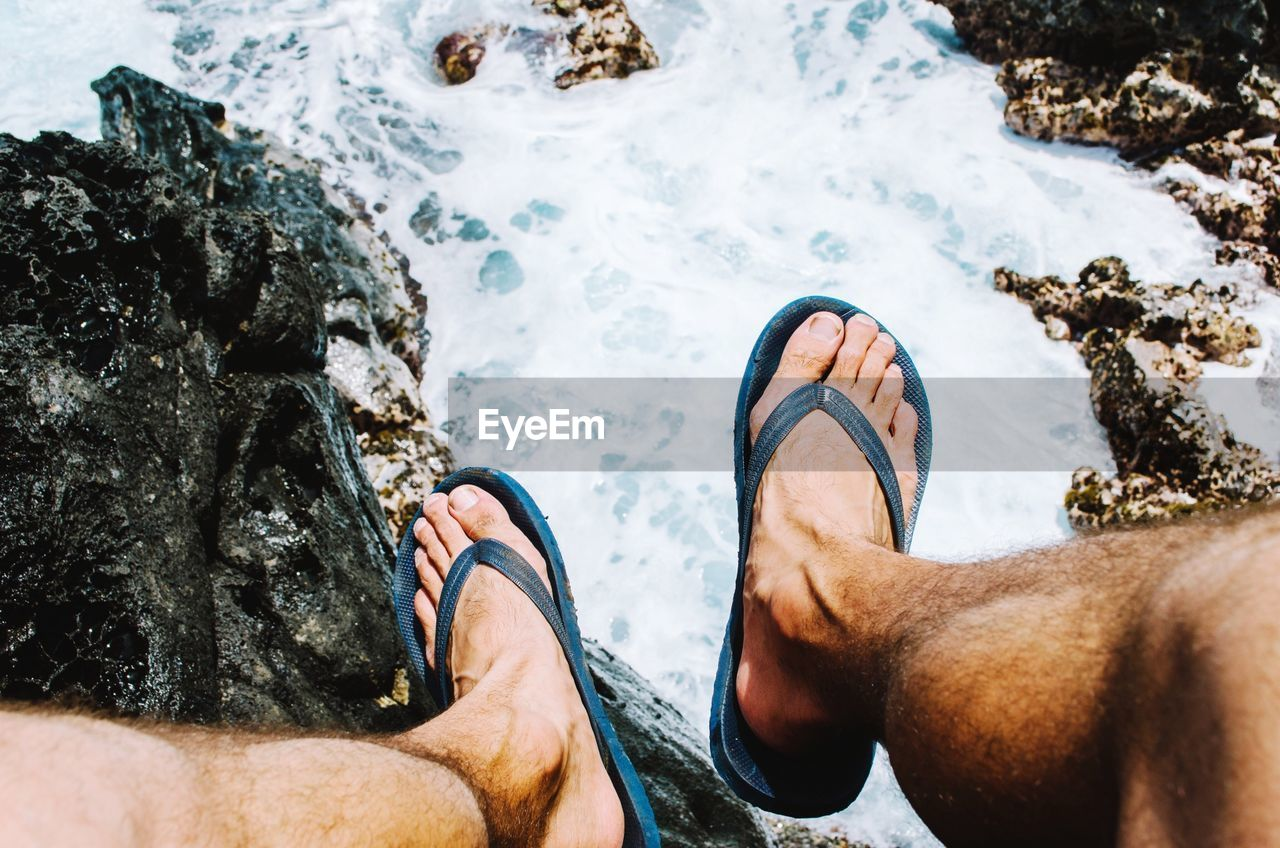 Low Section Of Man In Flip-Flops Against River Stream