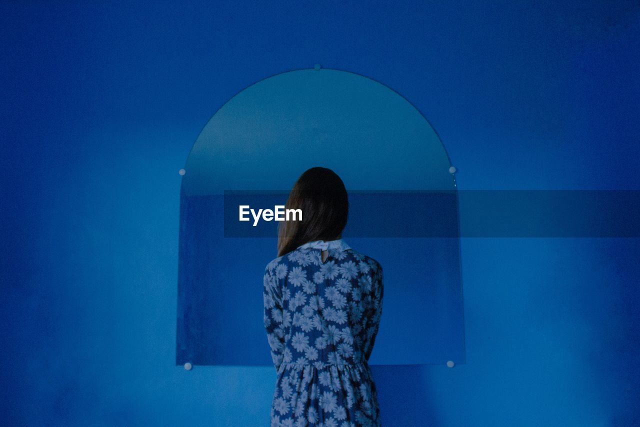 Rear View Of Woman Standing Against Mirror On Blue Wall