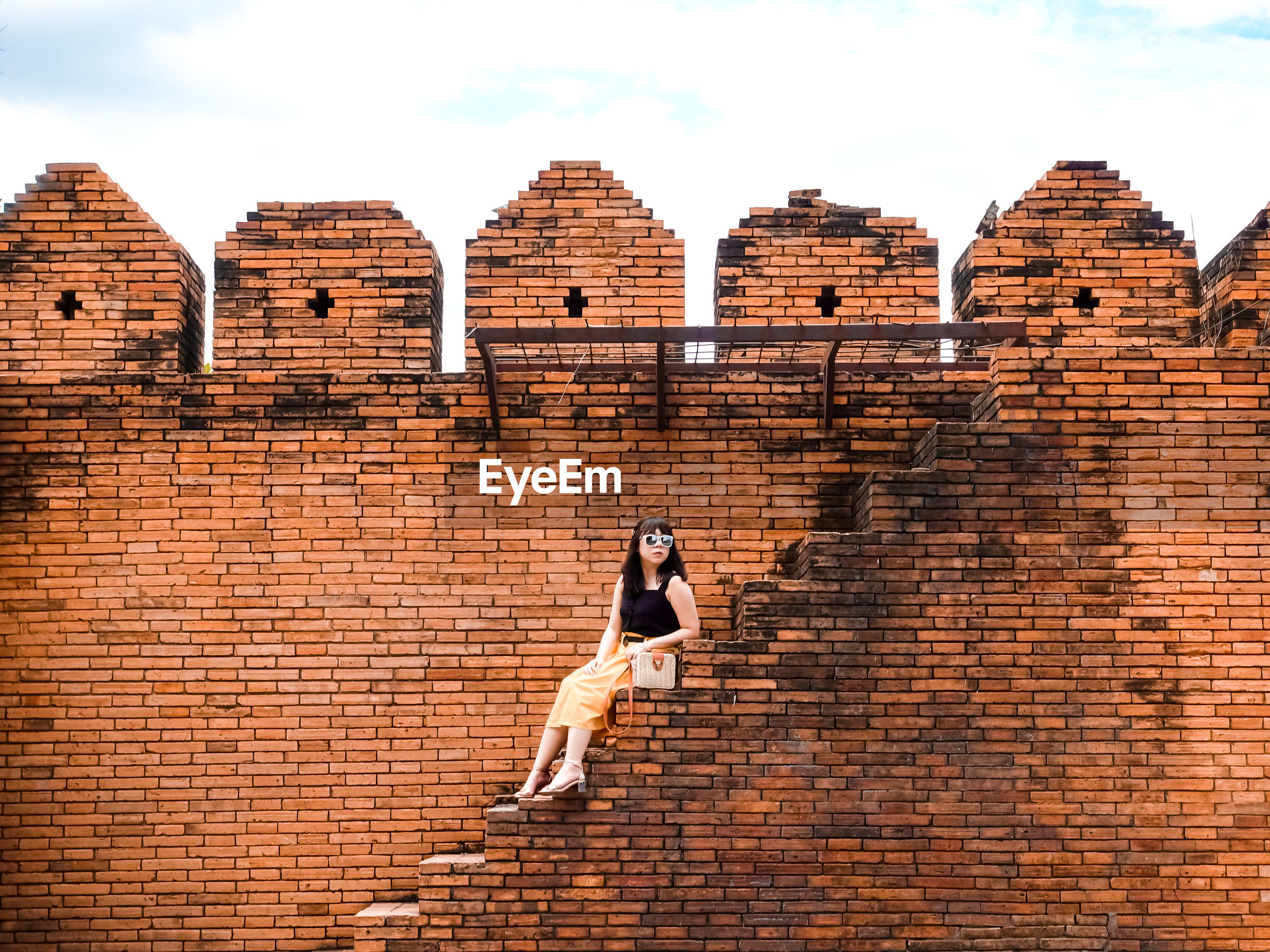 Full length of woman sitting on steps against brick wall