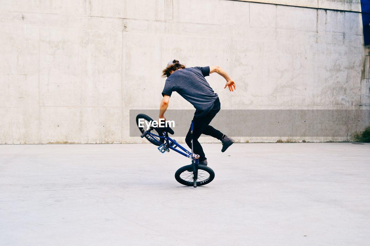 MAN RIDING BICYCLE ON UMBRELLA