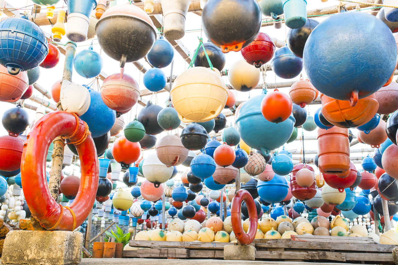 Low angle view of colorful buoys hanging for sale at market stall
