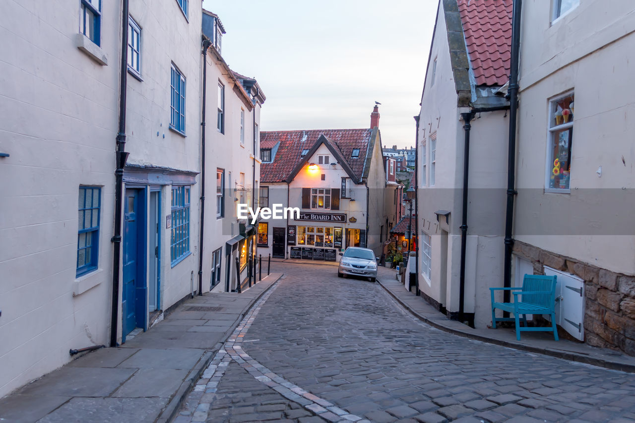 architecture, built structure, building exterior, building, residential district, city, street, house, direction, the way forward, footpath, no people, transportation, cobblestone, outdoors, window, sky, day, empty, nature, alley, row house