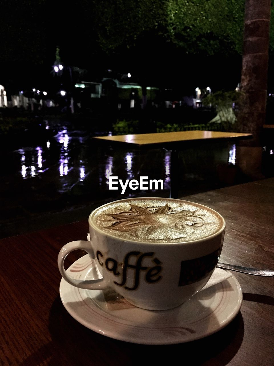 coffee - drink, coffee cup, drink, refreshment, food and drink, table, cappuccino, frothy drink, froth art, saucer, latte, water, illuminated, cafe, night, no people, freshness, close-up, mocha, tree, outdoors