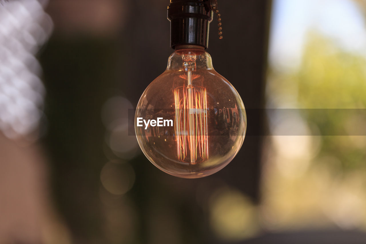 Close-Up Of Lit Light Bulb Against Blurred Background