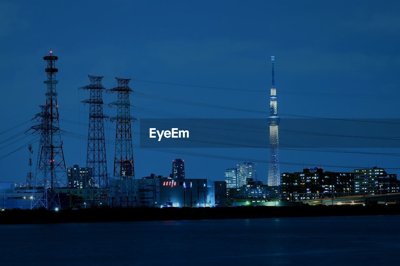 electricity, electricity pylon, fuel and power generation, tower, building exterior, built structure, illuminated, no people, architecture, night, waterfront, outdoors, industry, cable, sky, water, city, power station, nature