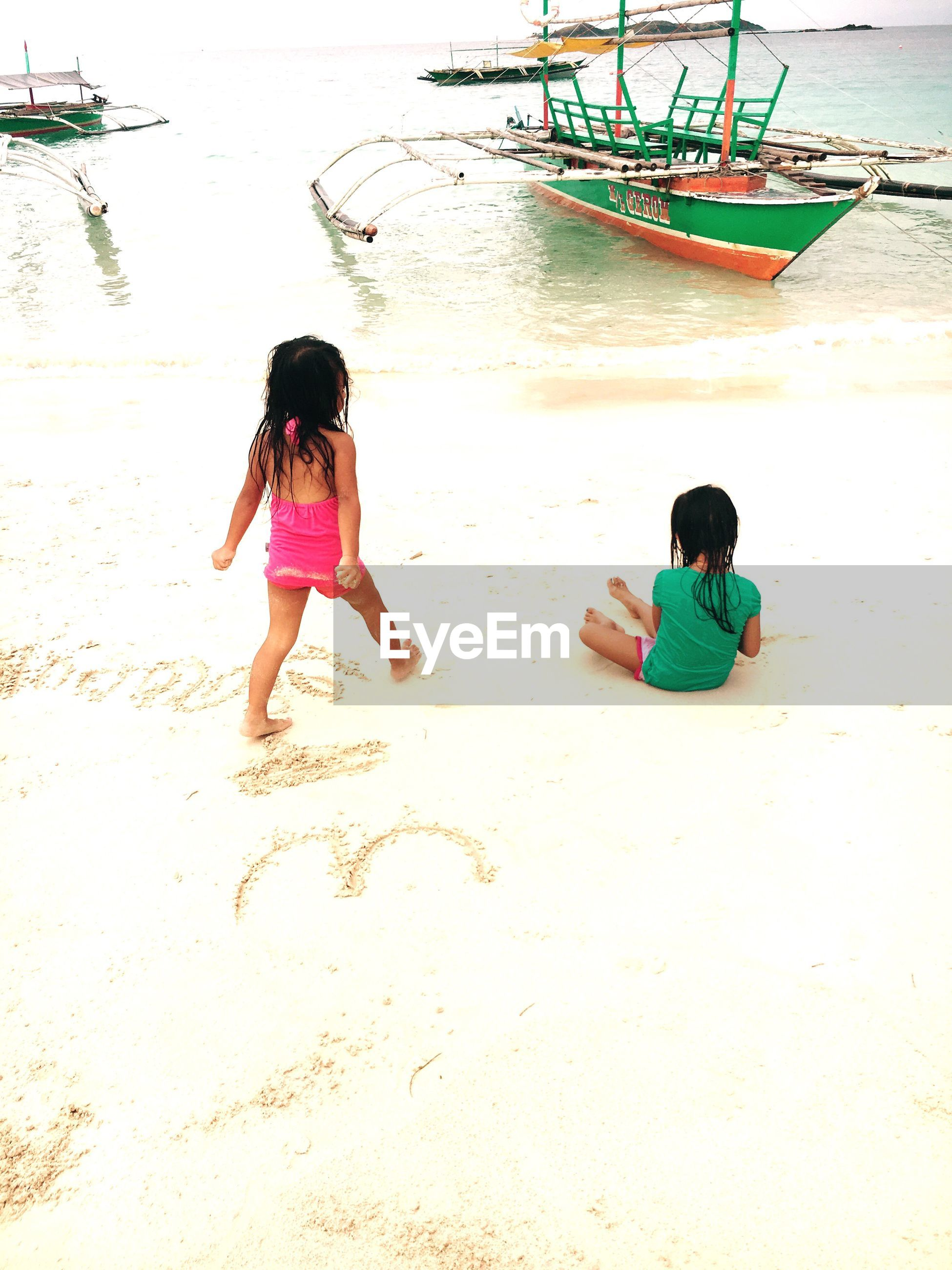 High angle view of girls at beach against sky