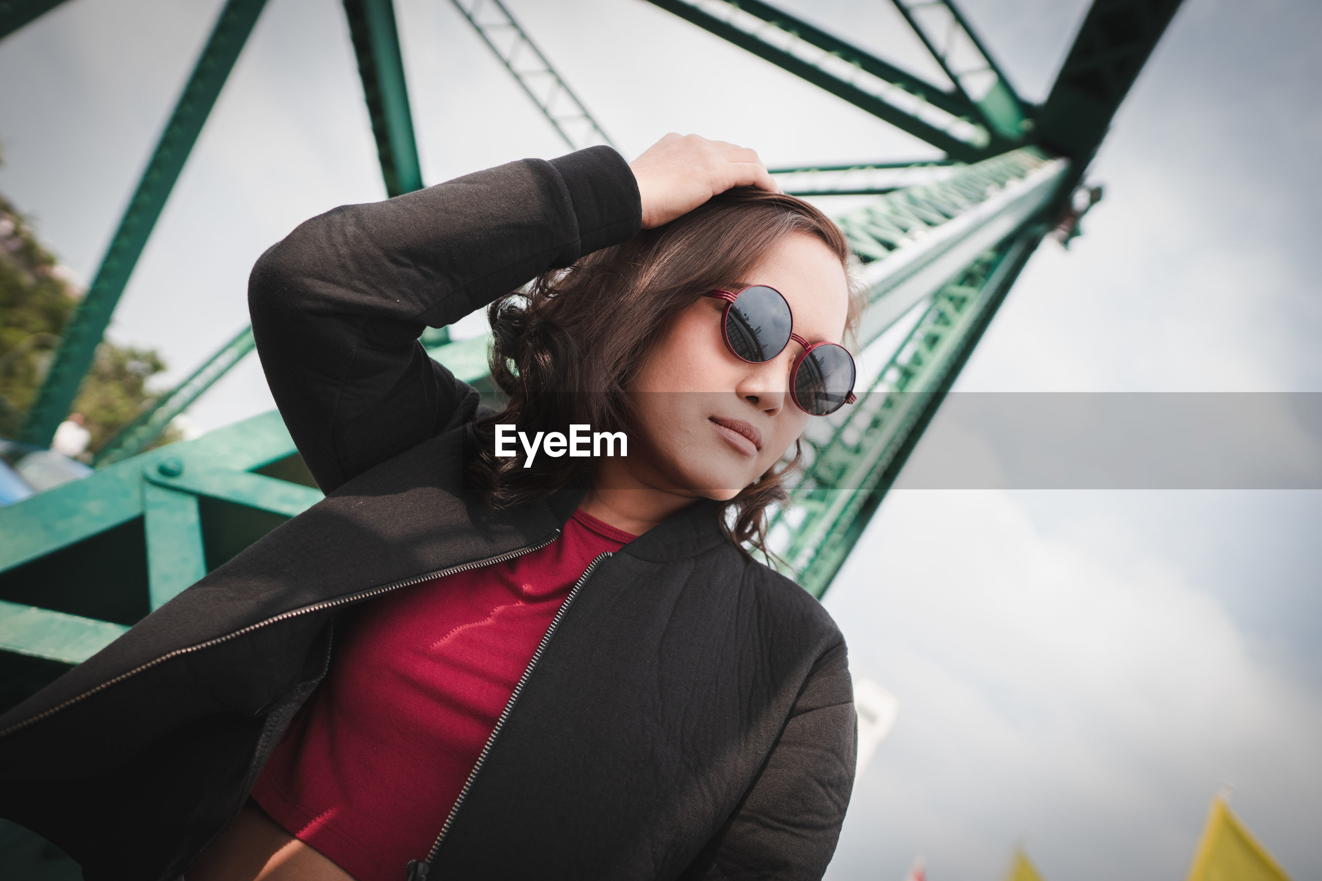 Woman wearing sunglasses against metallic structure and sky