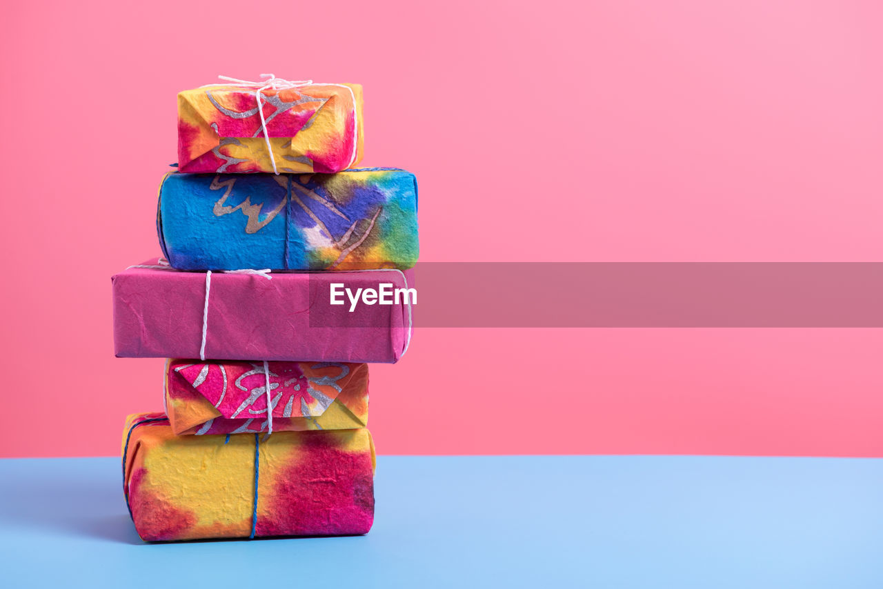 Stack Of Colorful Wrapped Gift Boxes Against Colored Background
