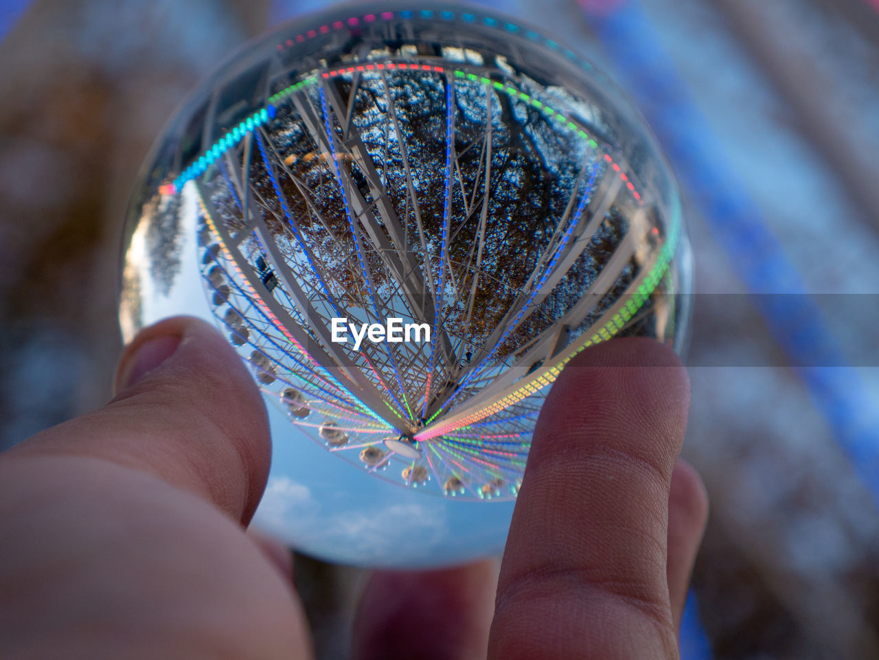 human hand, hand, human body part, holding, body part, one person, real people, finger, human finger, close-up, unrecognizable person, personal perspective, sphere, focus on foreground, lifestyles, leisure activity, selective focus, day, multi colored, outdoors, human limb