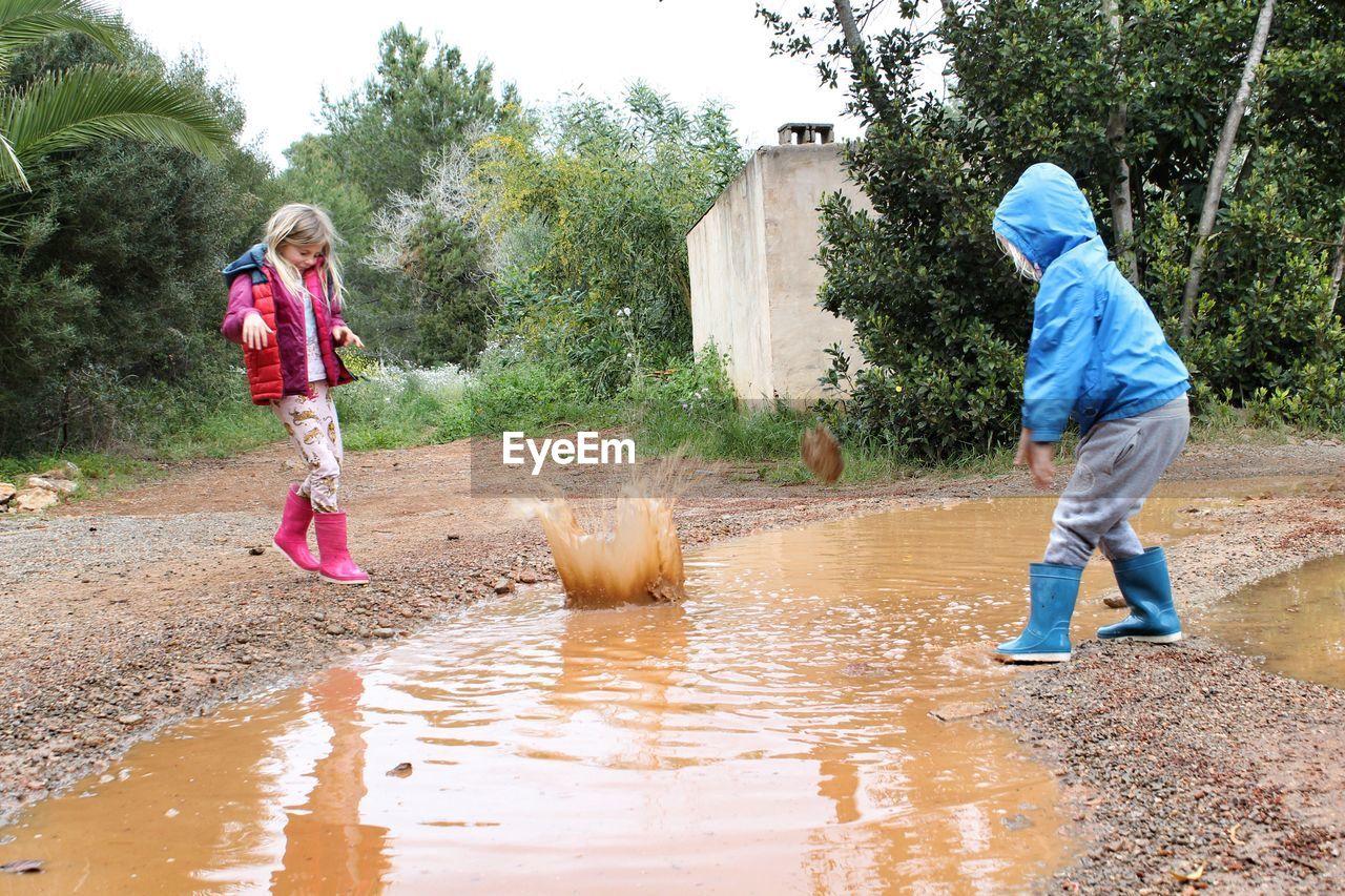 Full length of siblings splashing water during rainy season