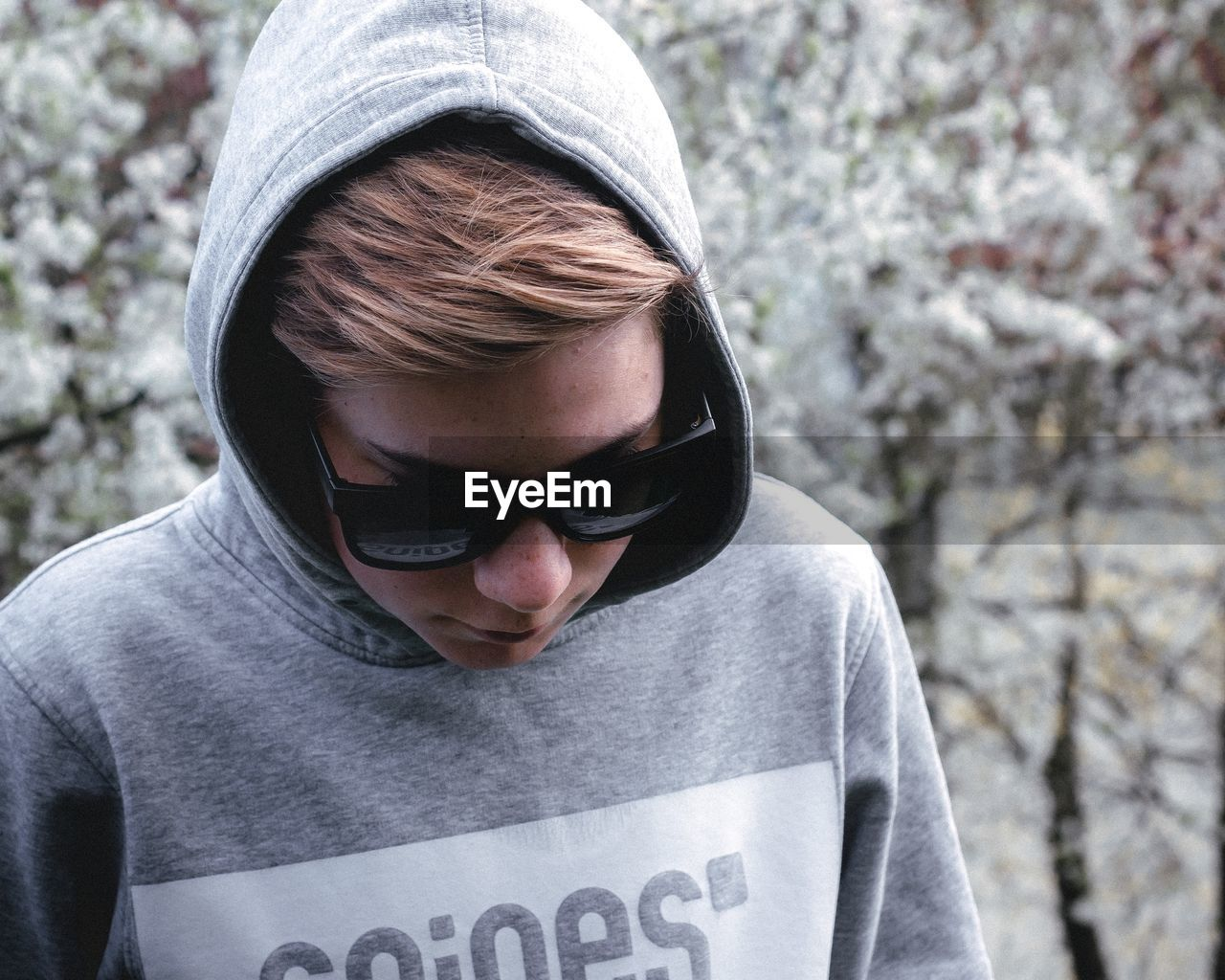 one person, front view, glasses, real people, focus on foreground, lifestyles, headshot, day, casual clothing, leisure activity, portrait, standing, text, waist up, hood, close-up, sunglasses, outdoors, hood - clothing, teenager, warm clothing