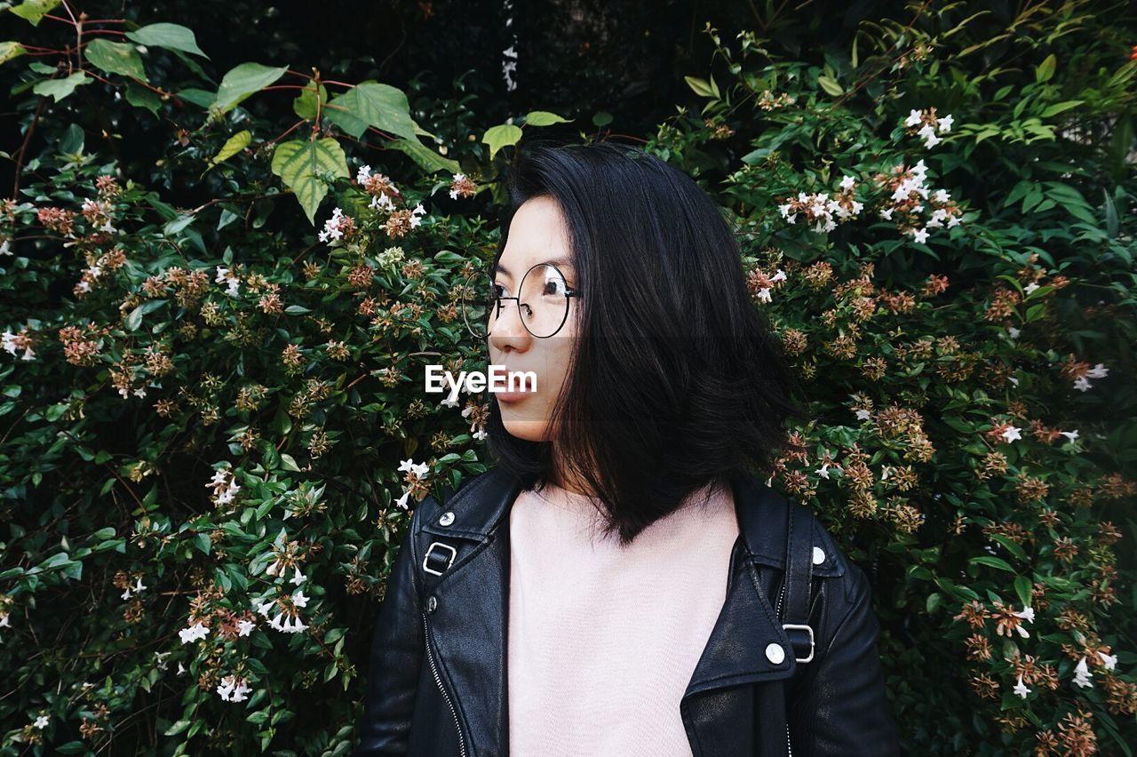 Portrait Of Beautiful Woman Against Plants