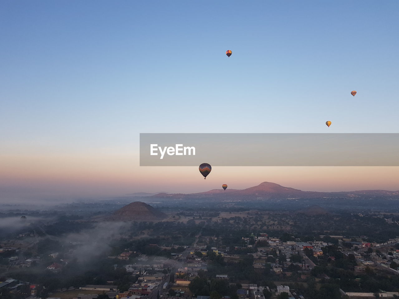 Hot air balloons flying in city against sky during sunrise