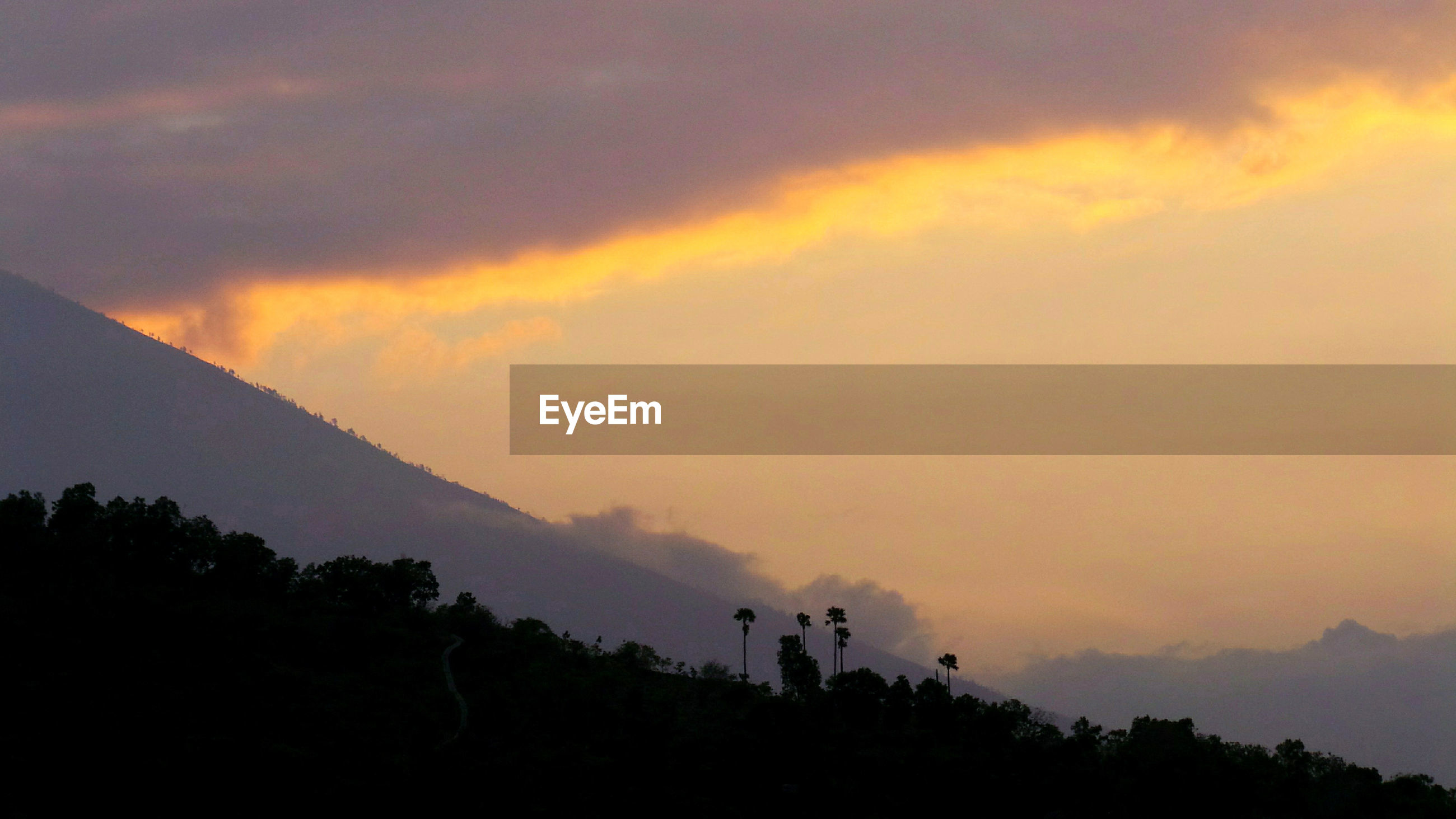 SILHOUETTE TREES AND MOUNTAINS AGAINST SKY DURING SUNSET