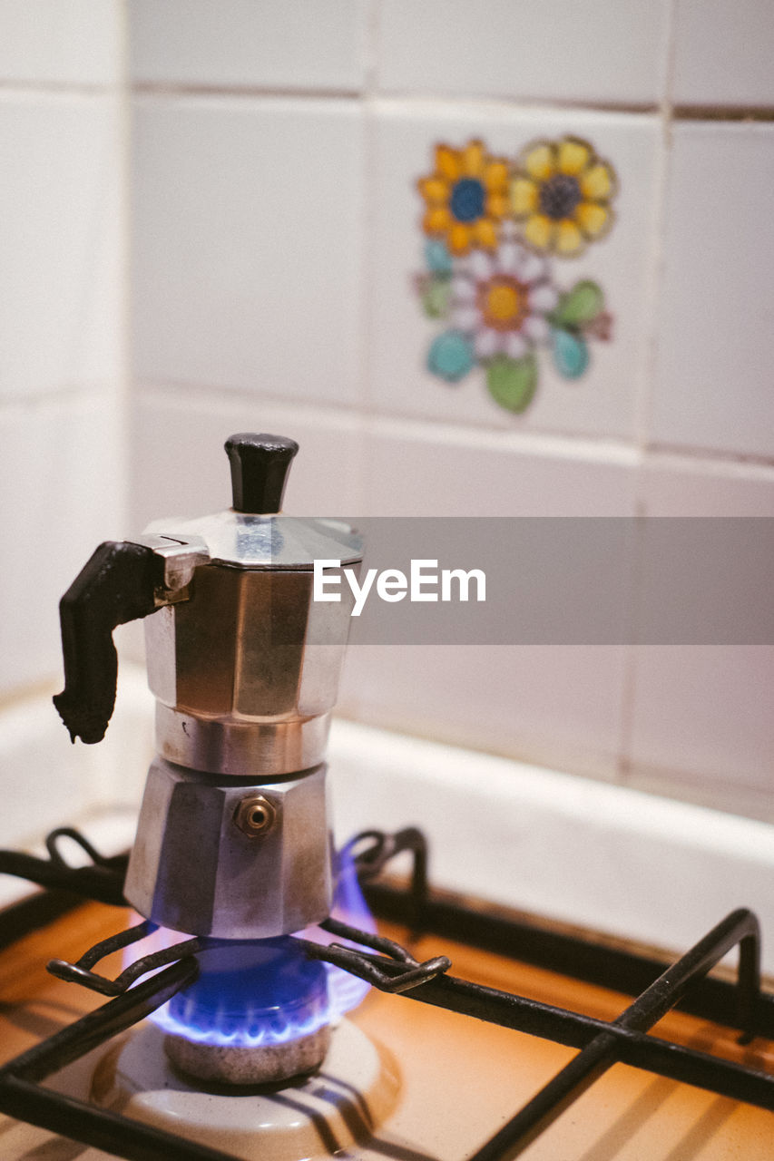 appliance, kitchen, indoors, domestic kitchen, domestic room, home, stove, no people, coffee maker, still life, focus on foreground, food and drink, burner - stove top, household equipment, tile, close-up, preparation, home interior, drink, espresso maker, coffee pot