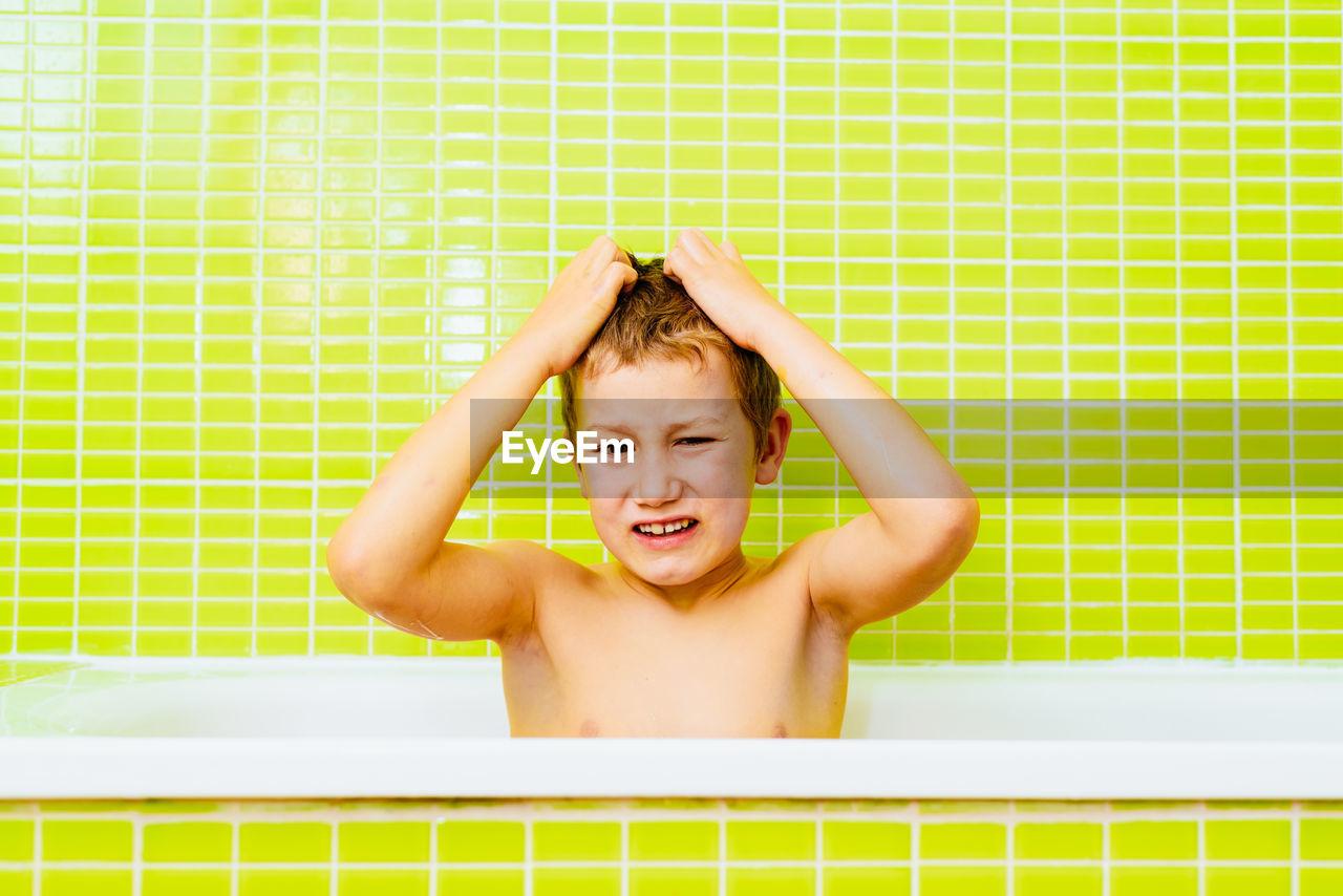 PORTRAIT OF HAPPY BOY IN BATHROOM