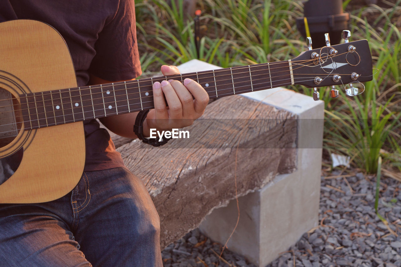 musical instrument, string instrument, guitar, music, one person, playing, real people, musical equipment, arts culture and entertainment, acoustic guitar, day, men, leisure activity, musical instrument string, wood - material, midsection, lifestyles, musician, sitting, focus on foreground, outdoors, plucking an instrument, hand, finger