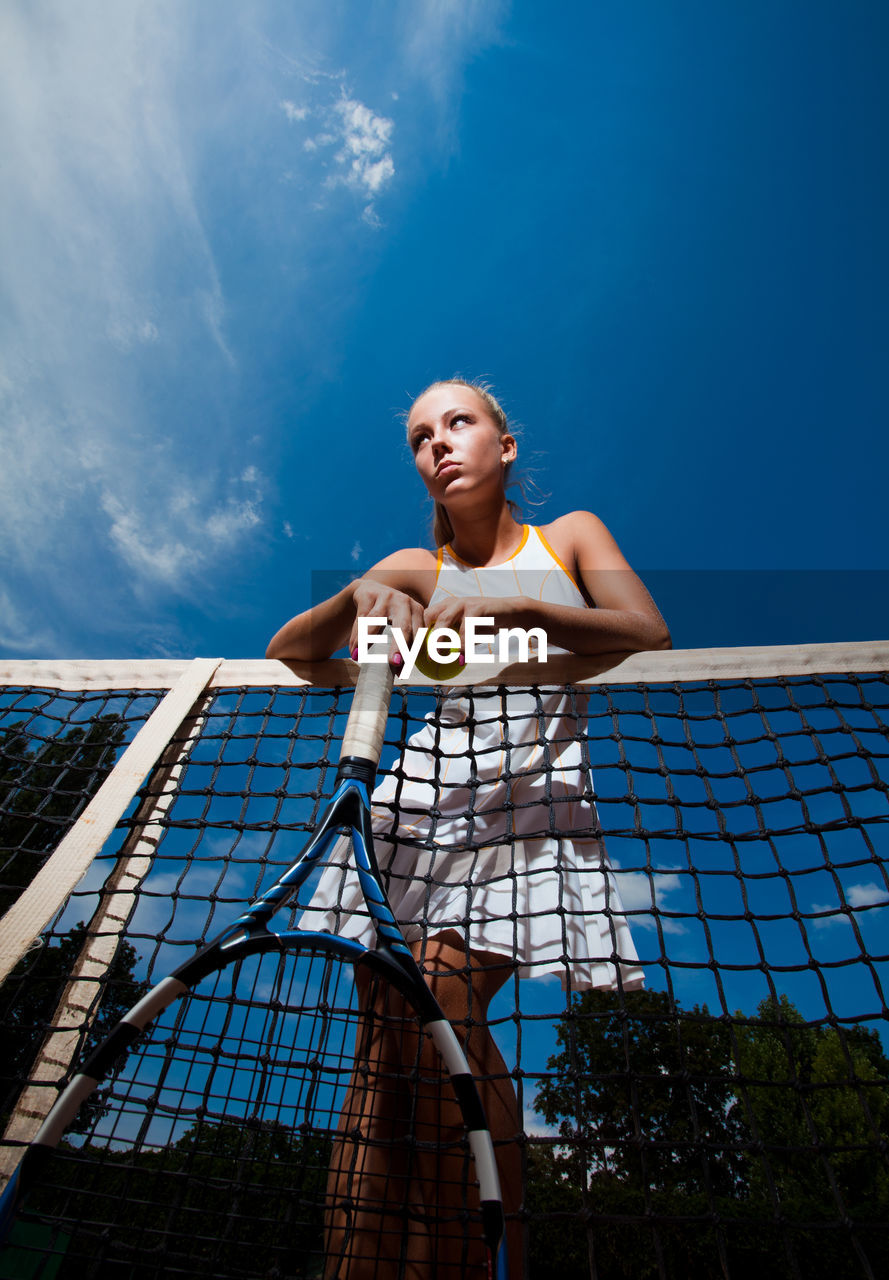 Low Angle Of Young Woman With Tennis Racket And Ball Standing By Net Against Blue Sky