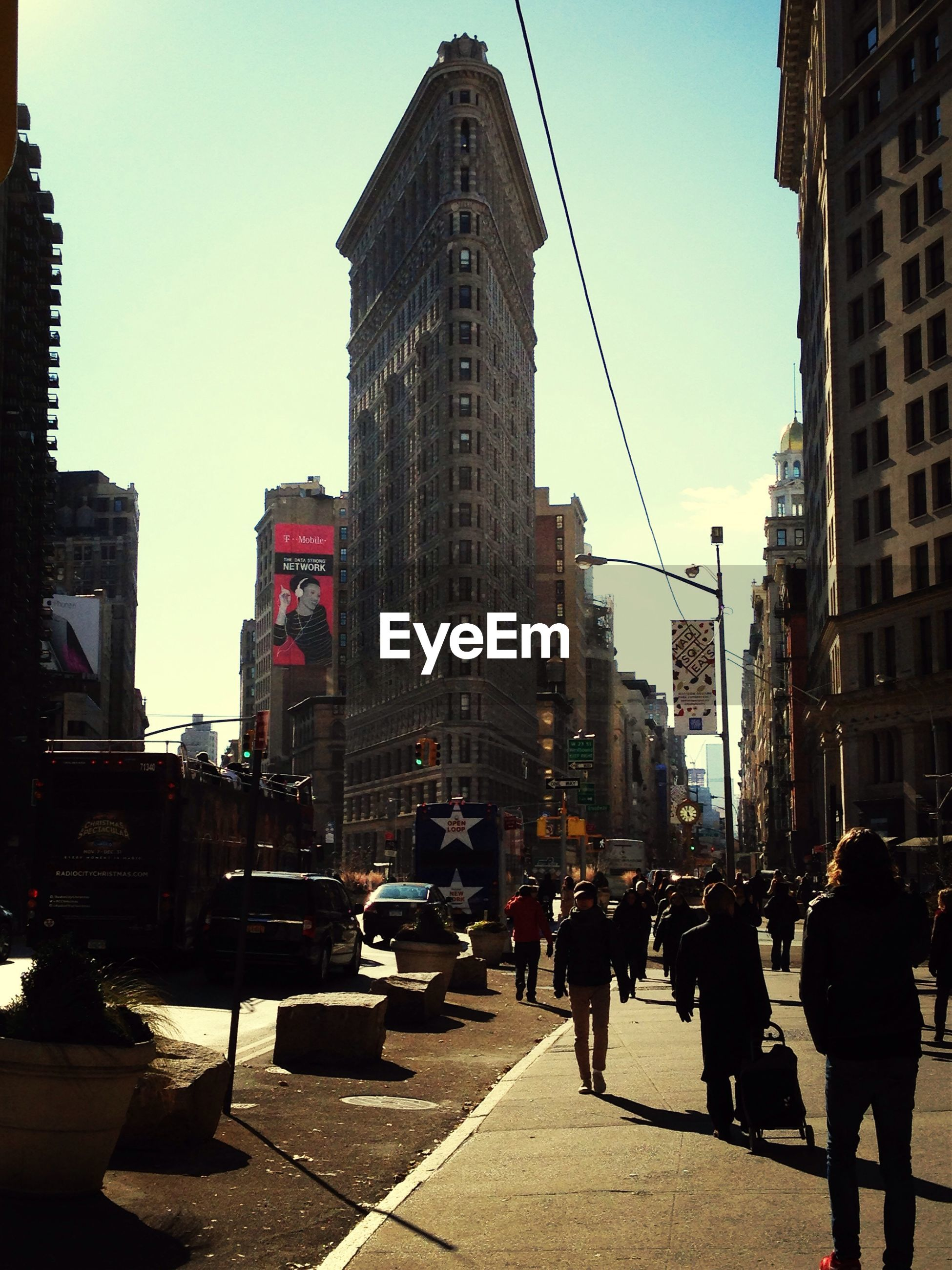People walking by flatiron building against clear sky