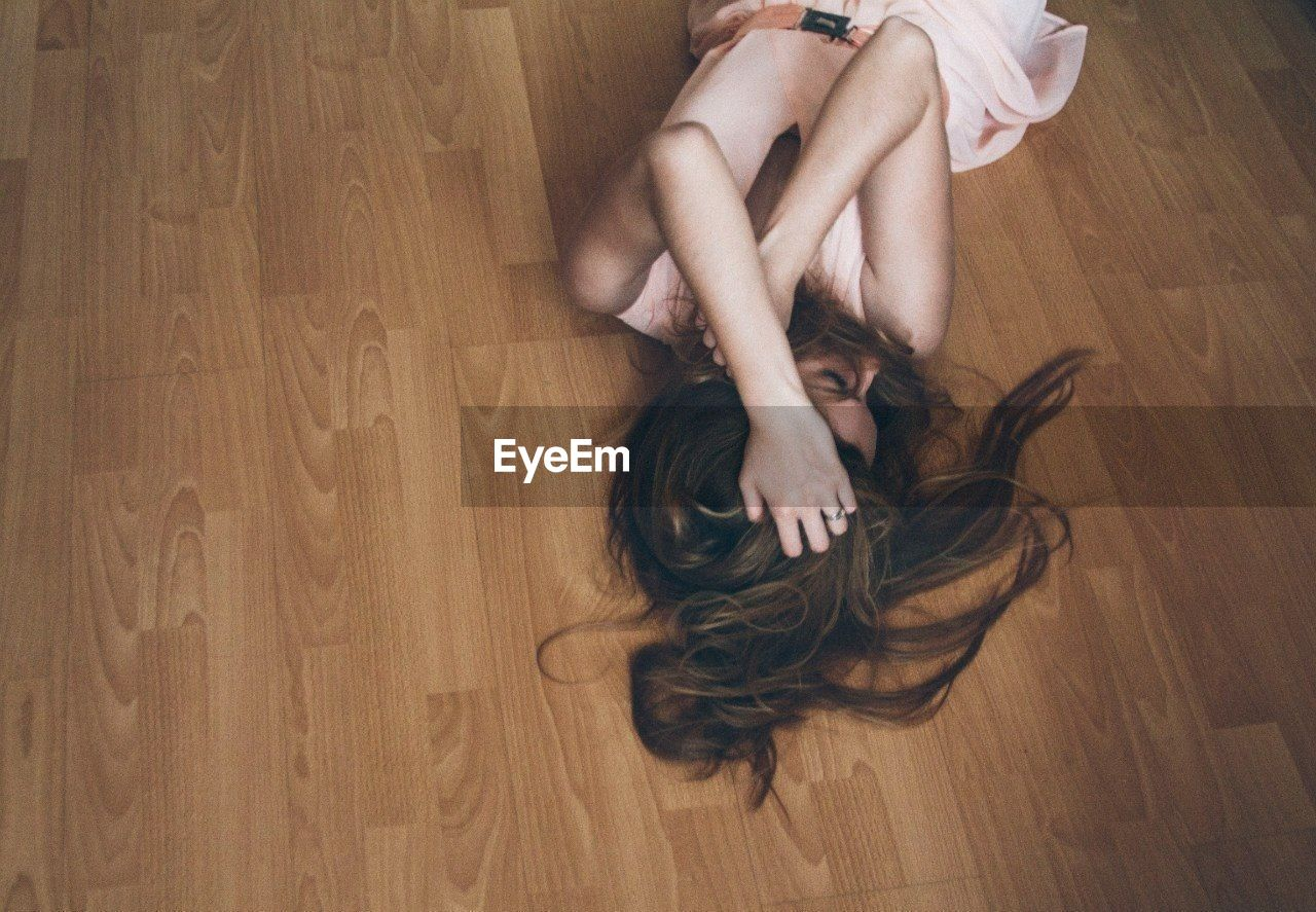 High Angle View Of Depressed Woman Lying On Hardwood Floor