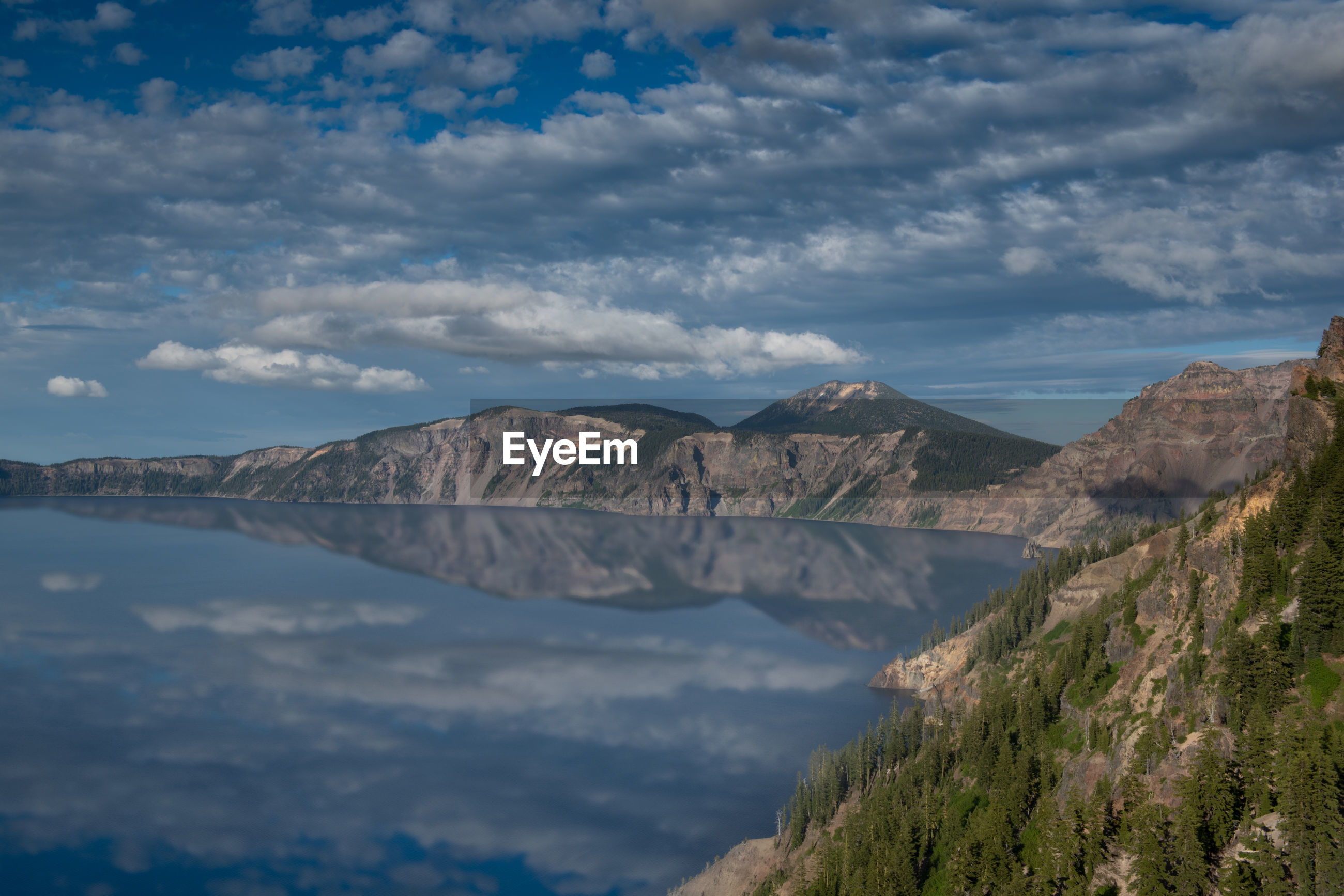 PANORAMIC VIEW OF SEA AND MOUNTAINS AGAINST CLOUDY SKY