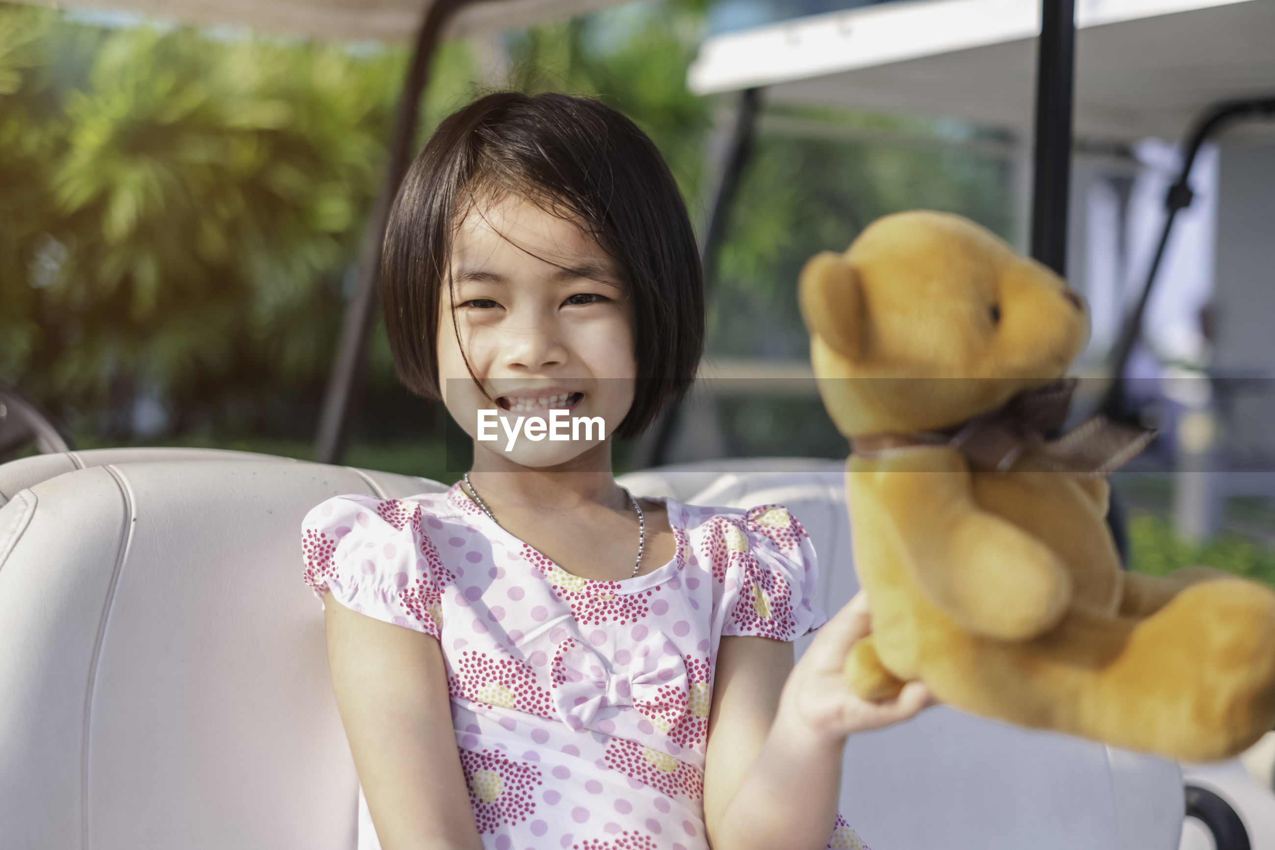Smiling girl sitting with teddy bear on golf cart