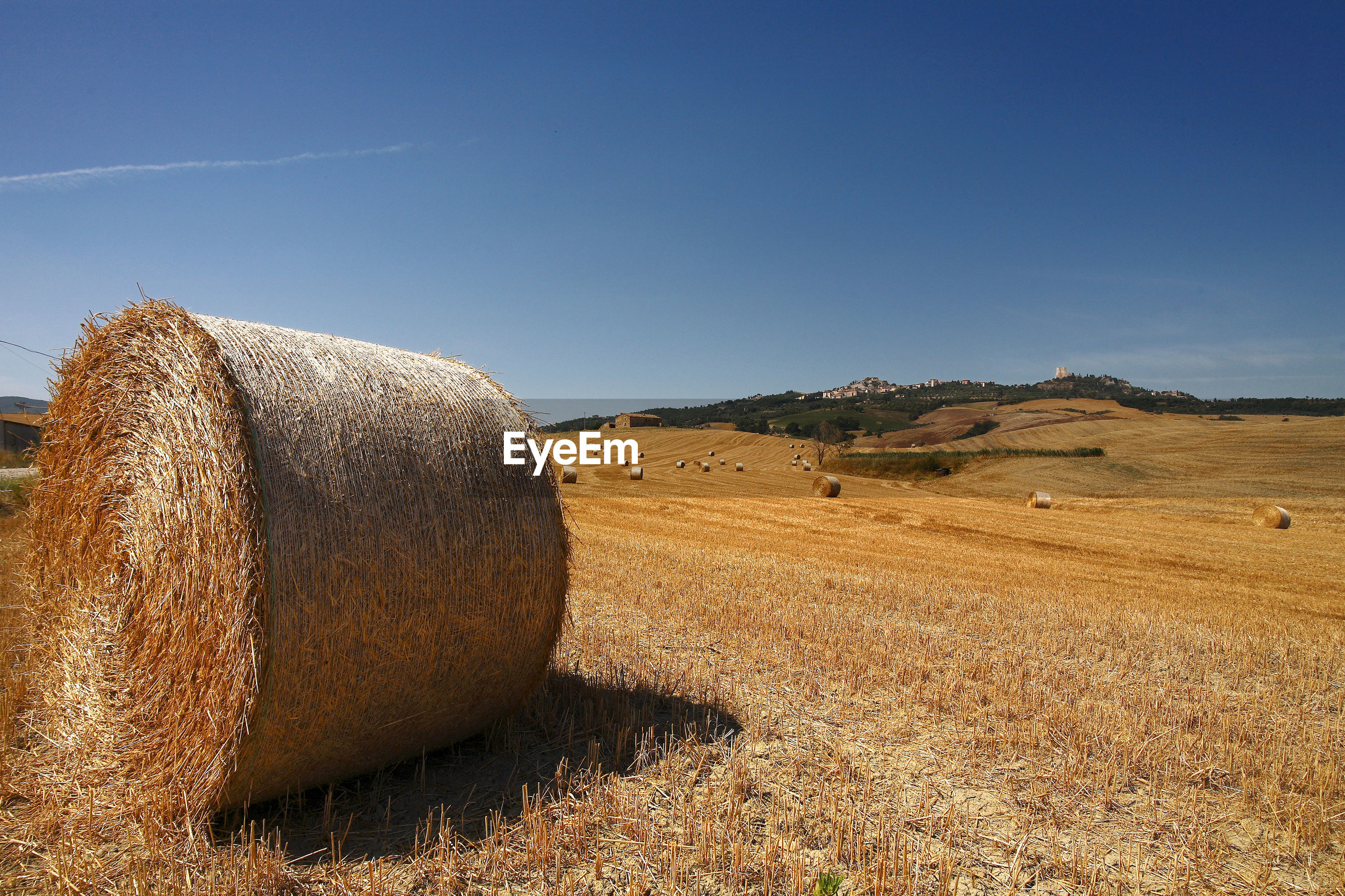 HAY BALES ON FIELD BY LAND AGAINST SKY