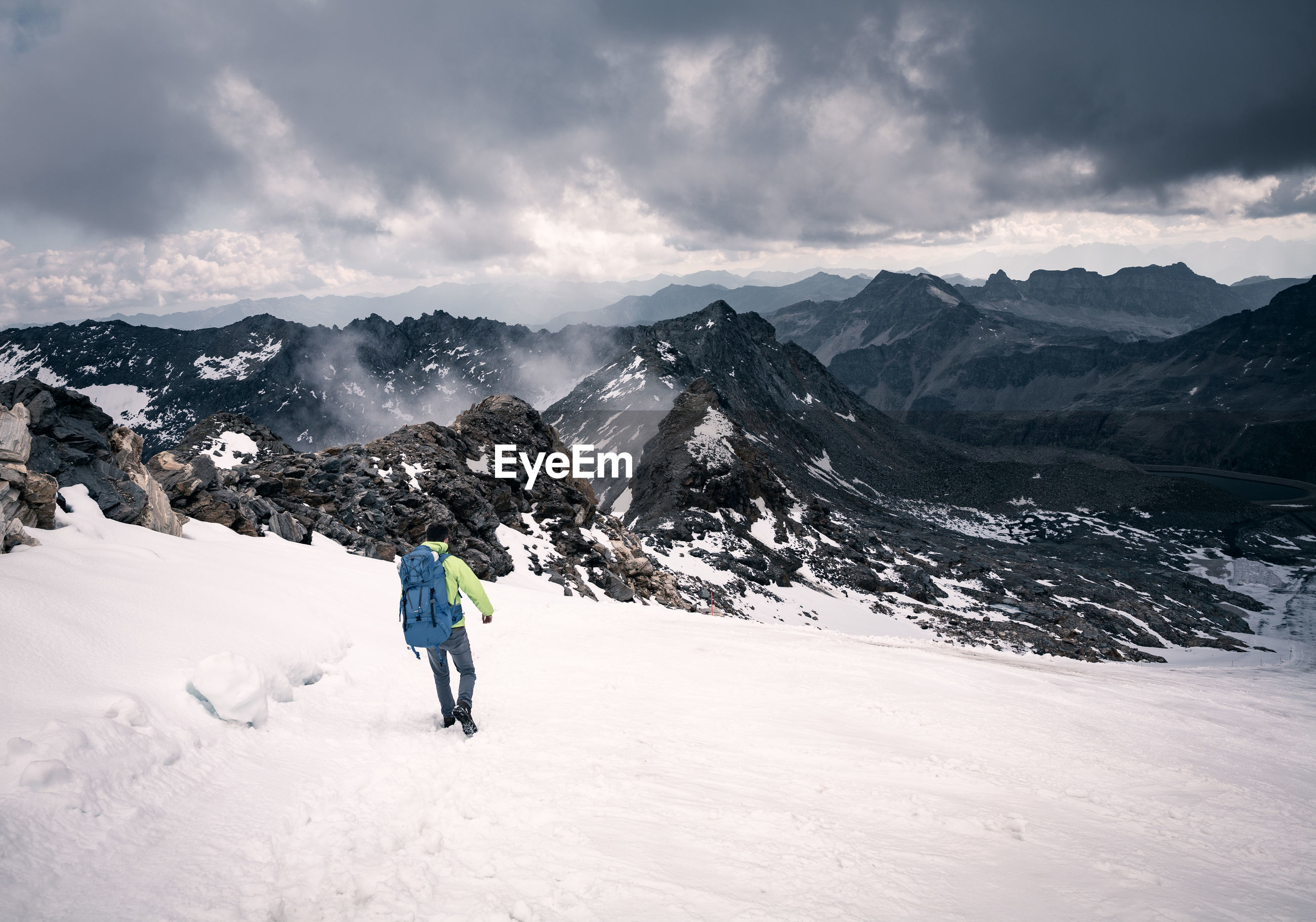 Rear view of backpacker on snowcapped mountains against cloudy sky