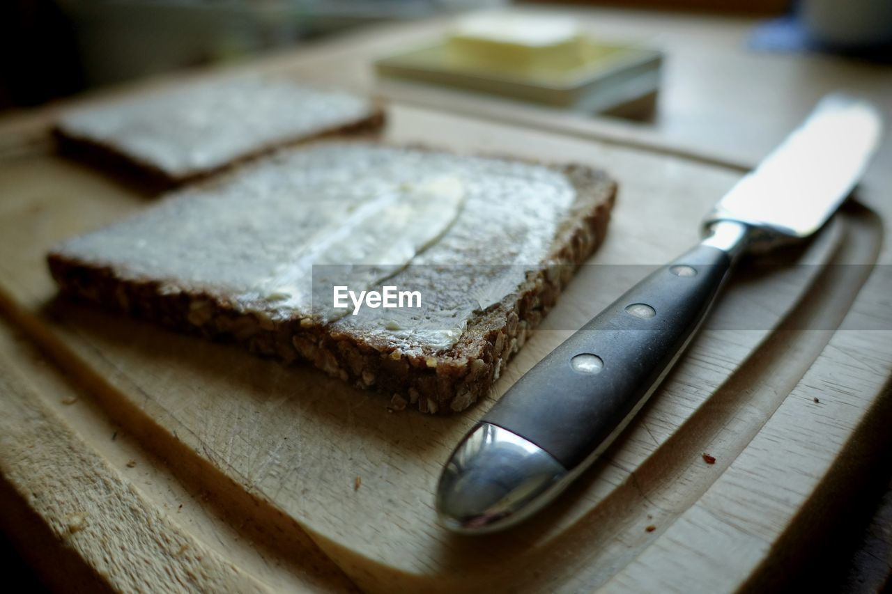 Knife By Bread With Butter On Cutting Board