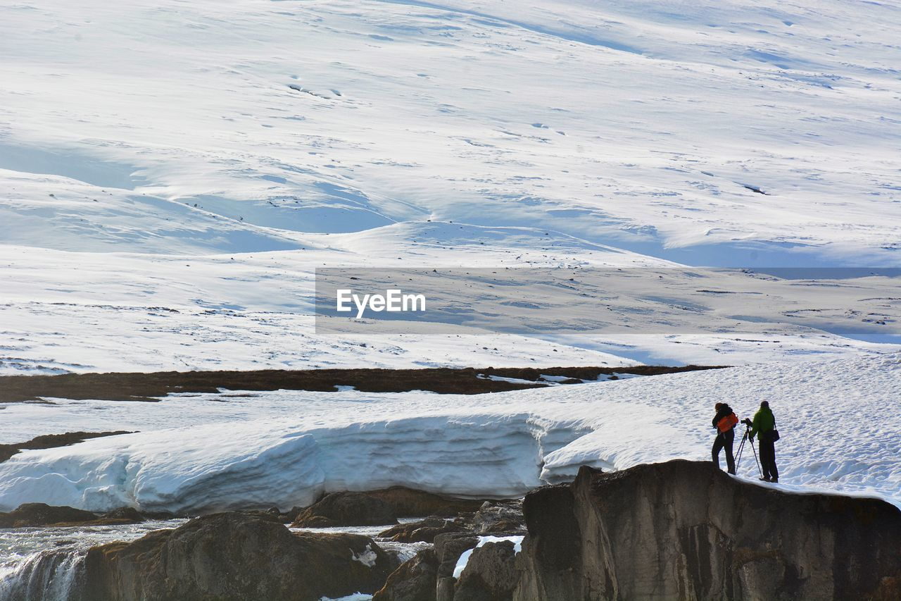 Men Standing On Snow Covered Landscape