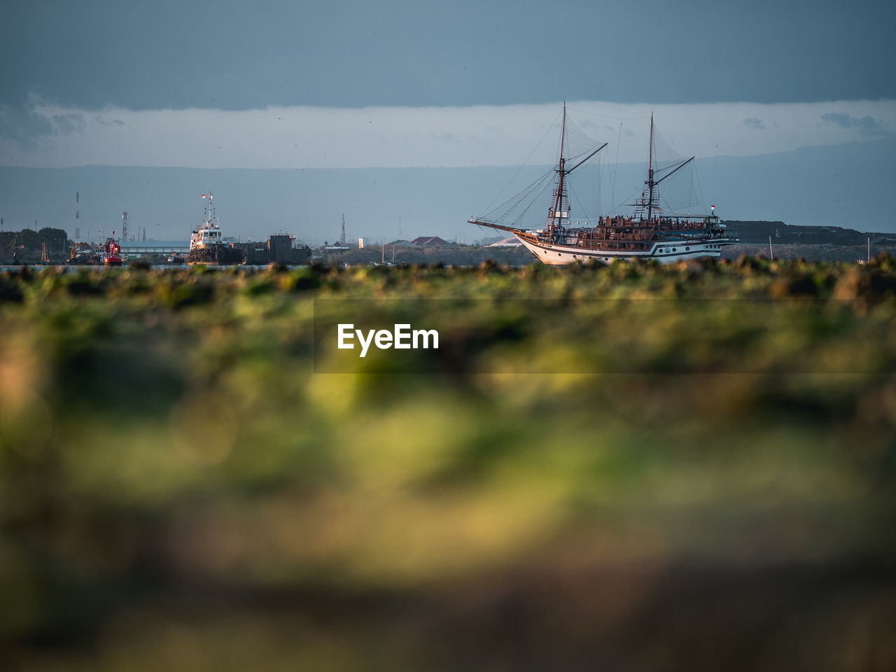 nautical vessel, mode of transportation, water, focus on background, selective focus, transportation, nature, sky, sea, day, no people, ship, architecture, outdoors, tilt-shift, moored, land, industry, scenics - nature