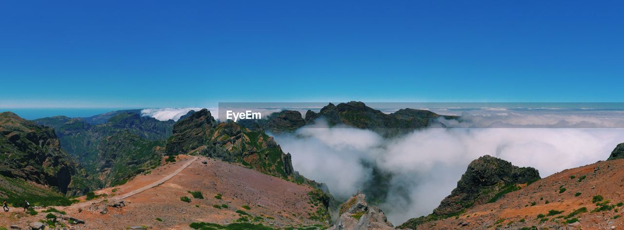 Scenic view of clouds covering mountains against blue sky