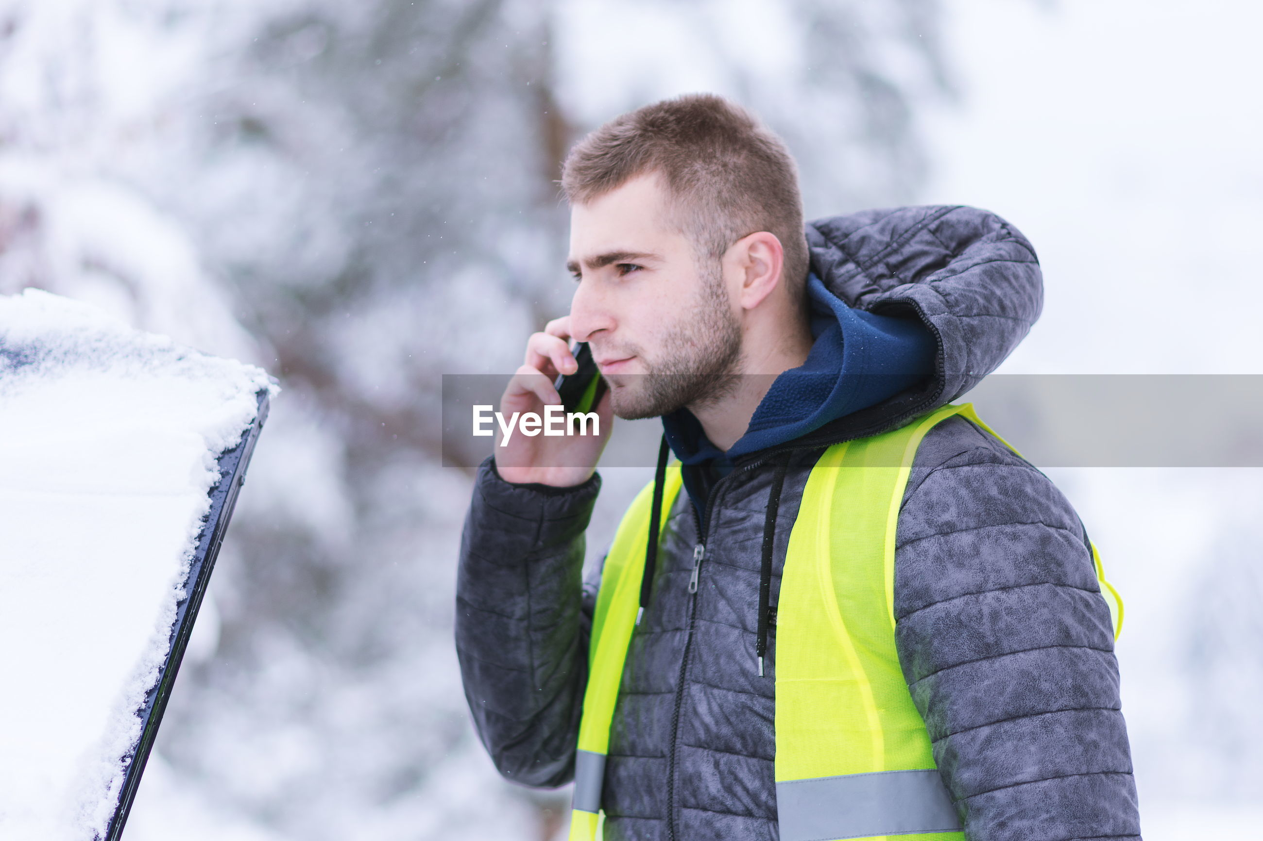 Side view of young man talking over smart phone while standing outdoors during winter