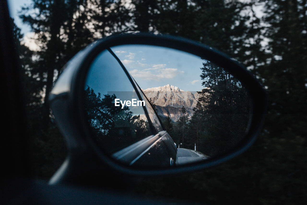 Reflection of mountain in side-view mirror