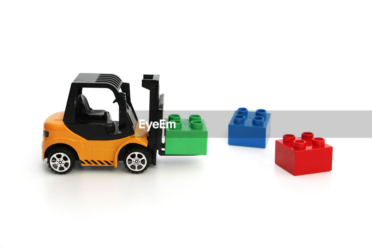 white background, studio shot, cut out, transportation, copy space, car, mode of transportation, no people, indoors, toy, still life, red, toy car, motor vehicle, container, group of objects, land vehicle, close-up, plastic, green color