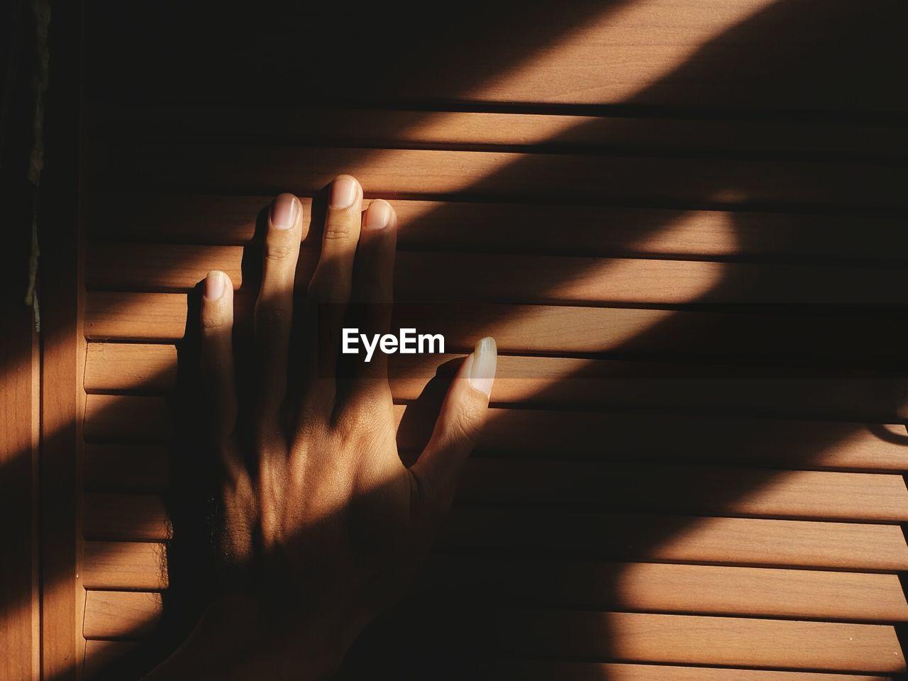 Shadow Of Hand On Window Shutter