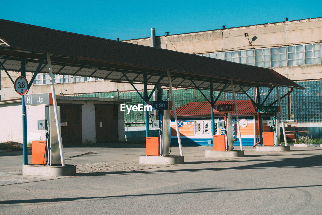 built structure, architecture, day, building exterior, sunlight, outdoors, transportation, no people, fuel pump, pay phone