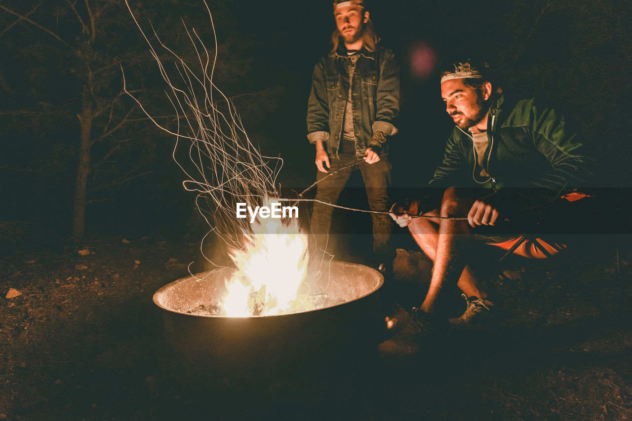 burning, fire, flame, fire - natural phenomenon, heat - temperature, two people, men, young adult, real people, glowing, night, lifestyles, young men, casual clothing, people, nature, males, togetherness, front view, bonfire, campfire