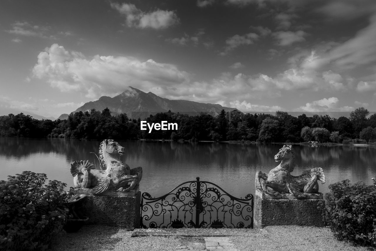 Gate and horse statues by lake against sky