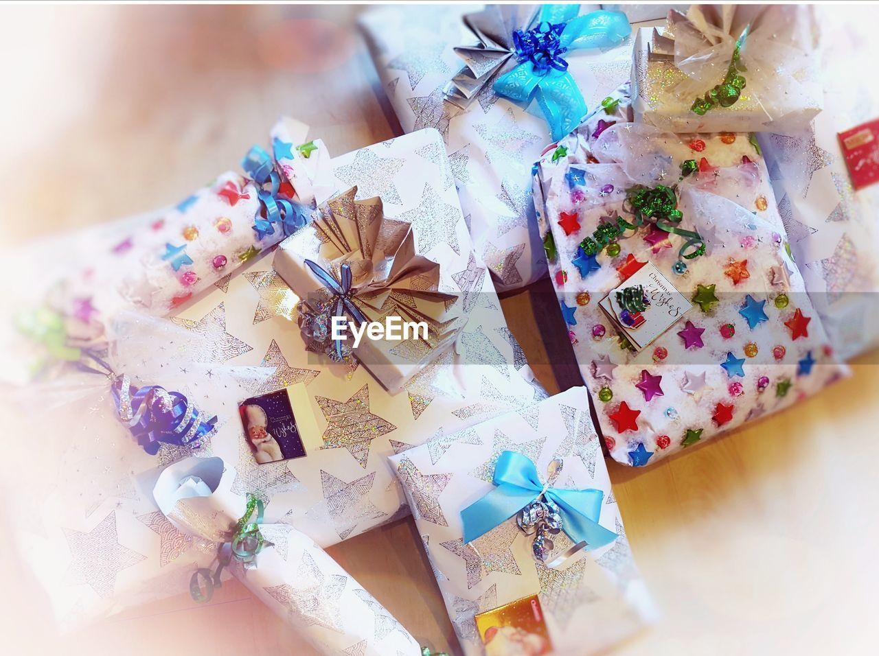 gift, still life, table, high angle view, indoors, celebration, gift box, close-up, ribbon, no people, paper, ribbon - sewing item, bow, directly above, choice, box, surprise, wrapped, box - container, christmas, wrapping paper, package, floral pattern, silver colored, temptation