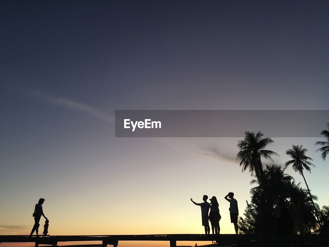 Silhouette friends standing on footbridge against sky during sunset