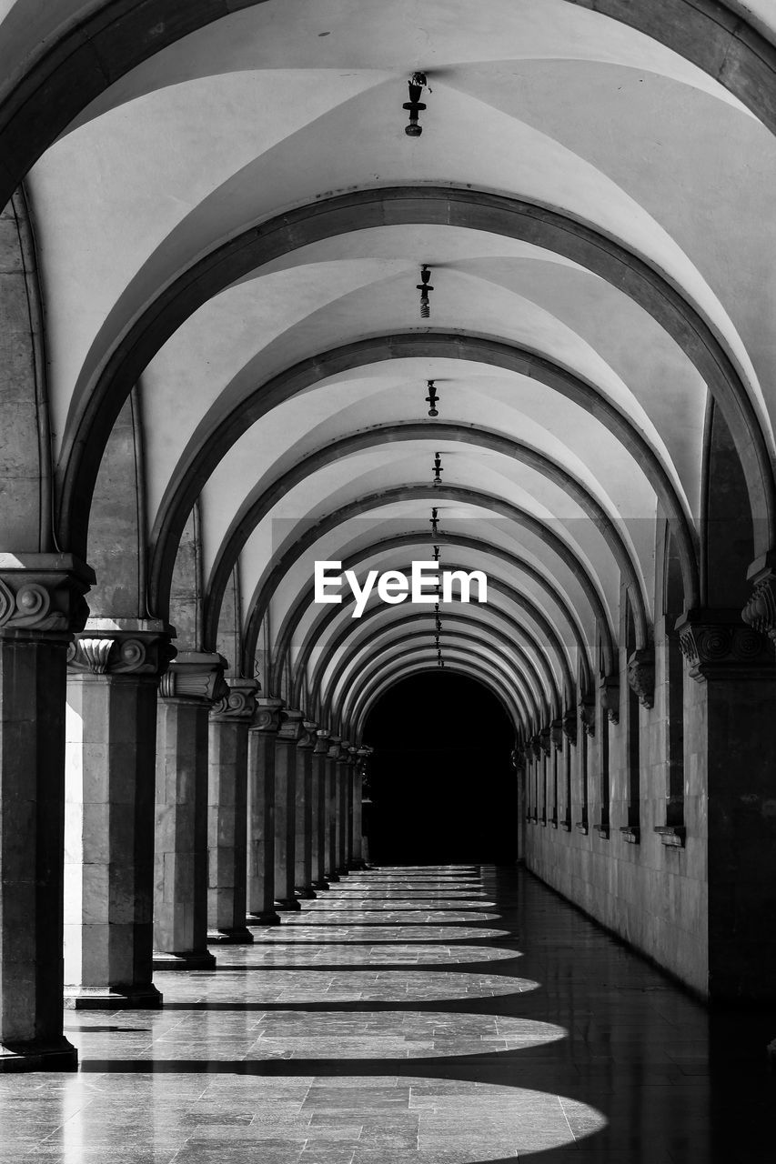 arch, architecture, the way forward, arcade, architectural column, direction, built structure, in a row, indoors, corridor, diminishing perspective, building, no people, colonnade, repetition, empty, day, lighting equipment, the past, ceiling, arched, long