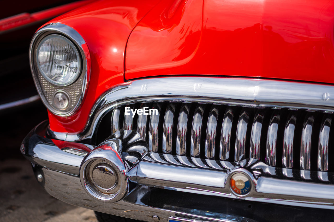 mode of transportation, land vehicle, motor vehicle, car, transportation, retro styled, red, headlight, metal, vintage car, shiny, no people, day, bumper, luxury, wealth, outdoors, chrome, lighting equipment, silver colored, antique, wheel