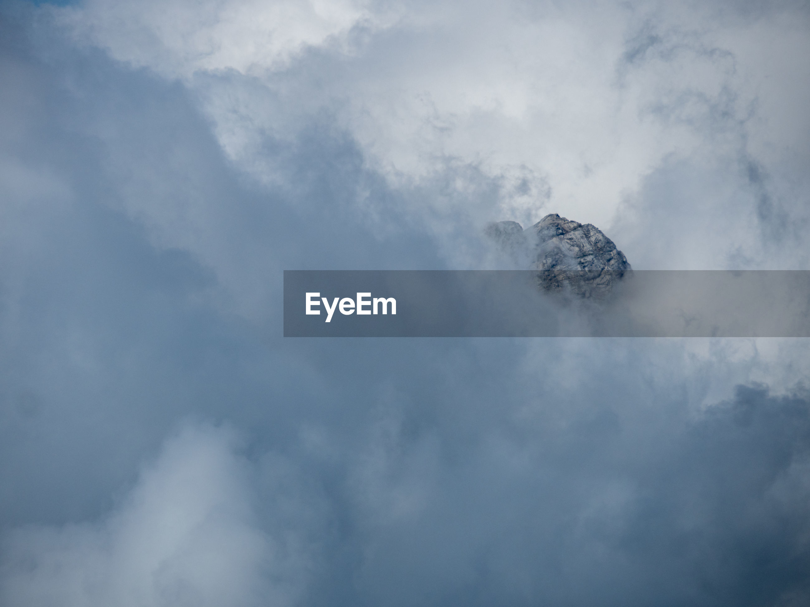 Low angle view of clouds against mountain and sky